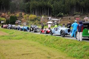 かやぶきの 里で一列に並ぶ車たち